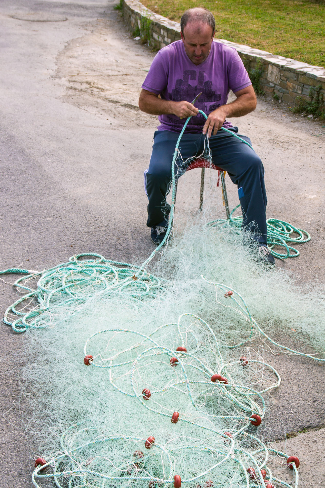 Fisherman fixing fishing net